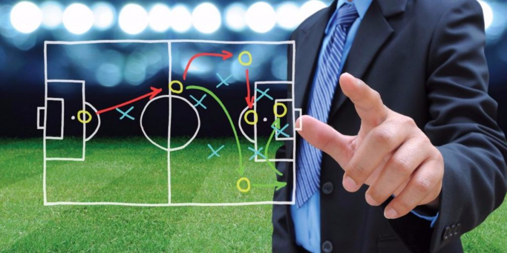 Man dress in suit behind the soccer game plan